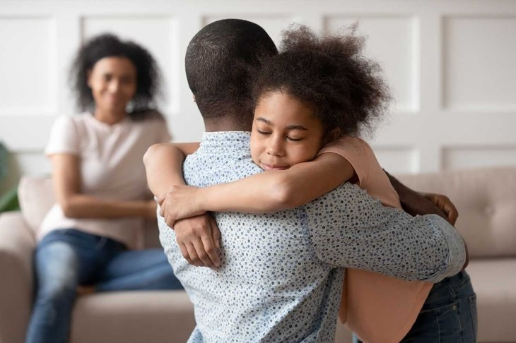 Young african american man holding, embracing, comforting smiling happy calm black cute kid daughter, blurred mother sitting on couch on background, loving supporting family concept.