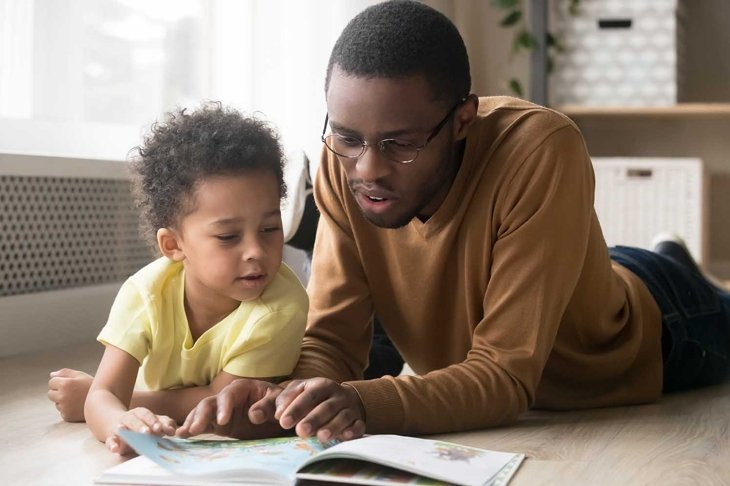 African American father in glasses and toddler son reading book together, lying on warm floor at home, black dad close up reading aloud fairy tale to adorable child, education, family weekend