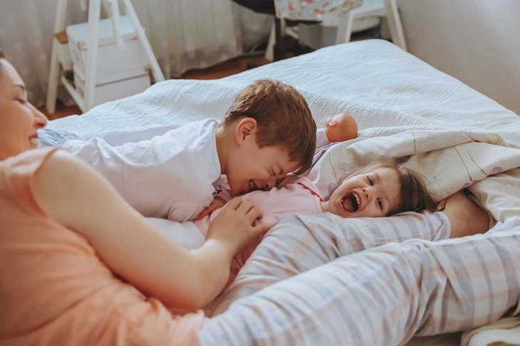 Closeup of happy family playing over the bed in a relaxed morning. Weekend family leisure time concept.