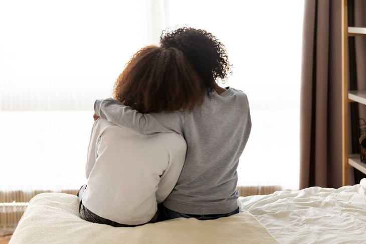 Rear back view black mother and daughter embrace sitting on bed at home, older sister consoling younger teen, girl suffers from unrequited love share secrets trustworthy person relative people concept
