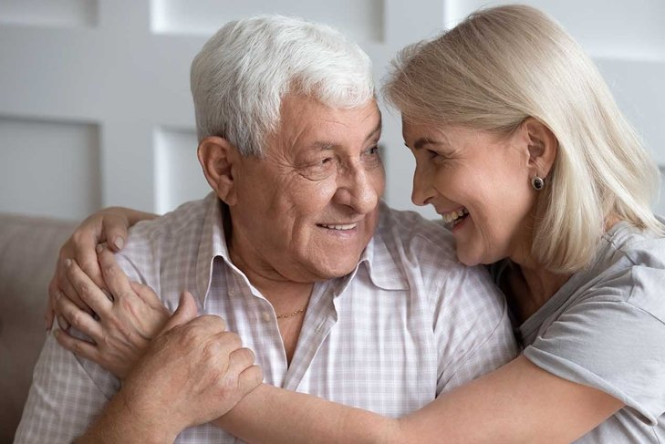 Happy older wife and husband hugging, looking in eyes, expressing love and support, family enjoying tender moment together, sitting on cozy sofa, mature father and middle-aged daughter close up