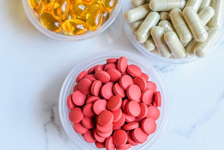 Close up Vitamins and Supplements Background consist of Iron Dietary Supplement, Neem herbal Supplement, Cod Liver Oil Dietary Supplement on a marble background.