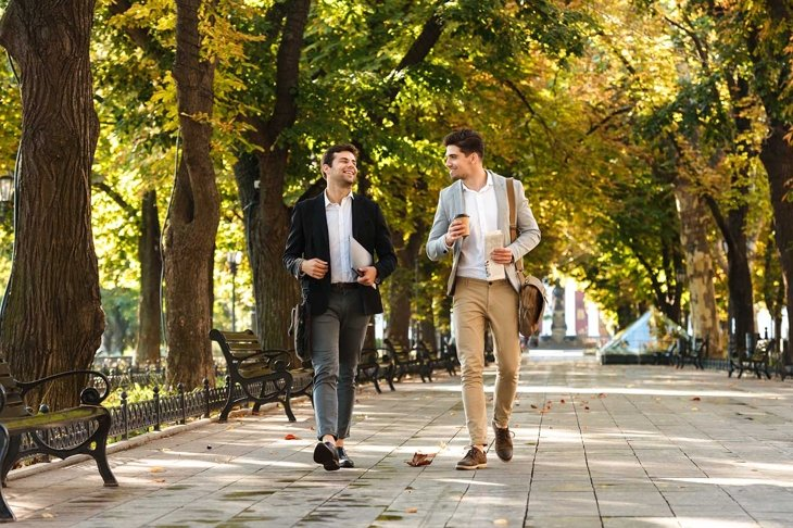 Photo of young businessmen in suits walking outdoor through green park with takeaway coffee and laptop during sunny day