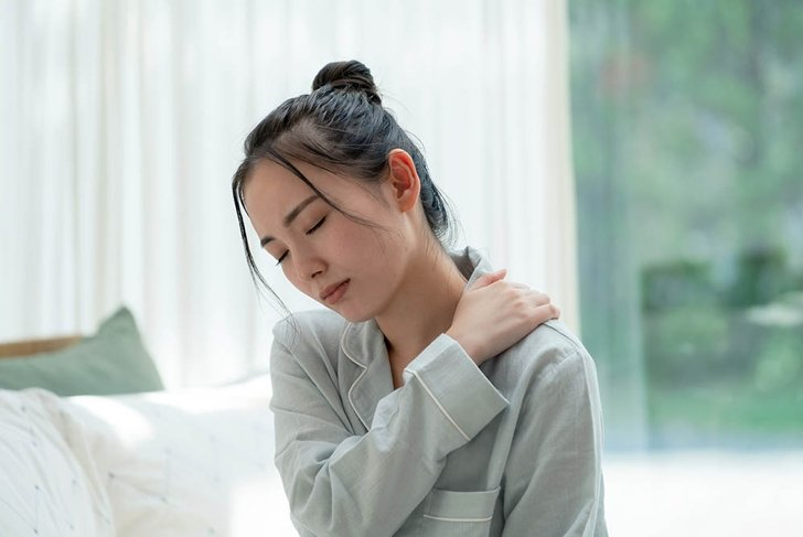Depressed young asian woman in bedroom.