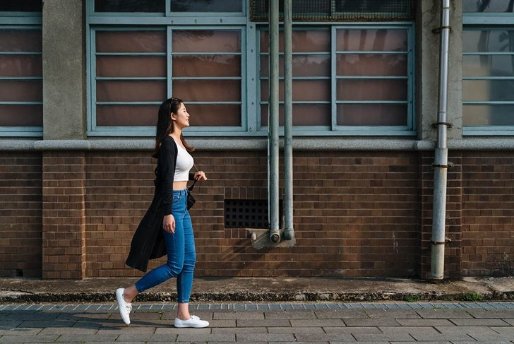 attractive asian woman with cute smile in stylish crop top in fashion blue jeans walking on street in old city near vintage red brick wall. side view full length beautiful girl relax enjoy sunshine