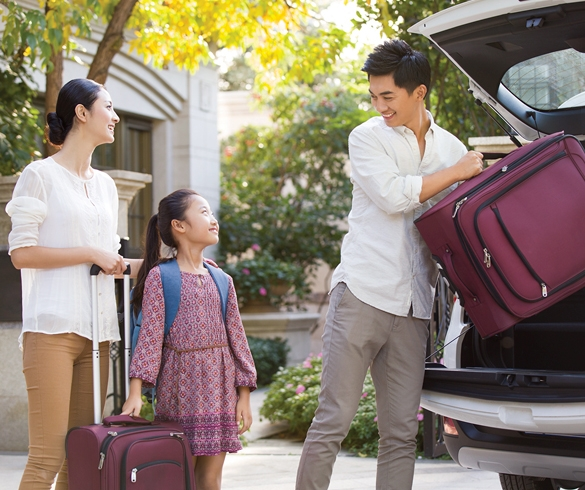 Man, woman and child loading car with luggage - 12445
