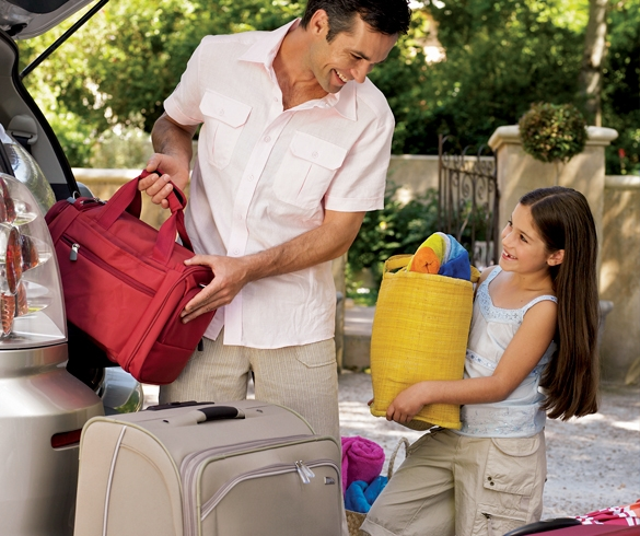 Man and child carrying luggage to a car - 11561