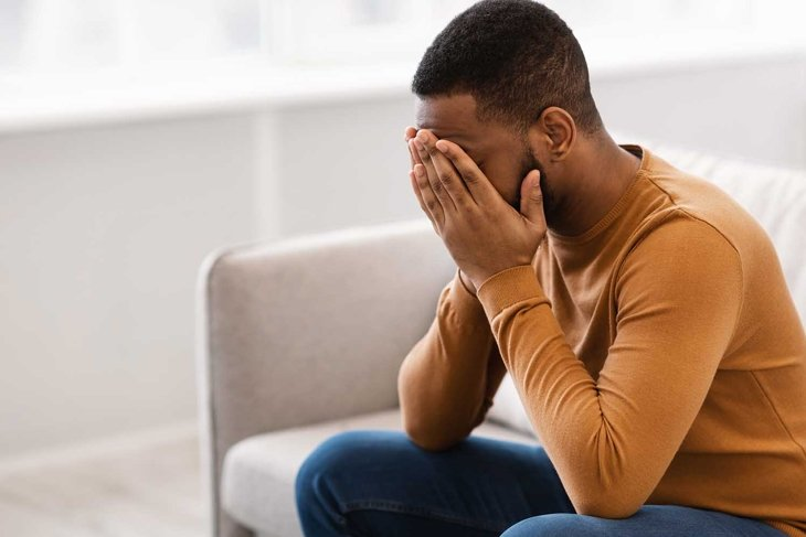 Male Depression. Desperate Depressed African Man Covering Face Crying Having Problems Sitting On Couch At Home. Emotional Stress And Unhappiness Concept. Despair, Grief And Negative Emotions