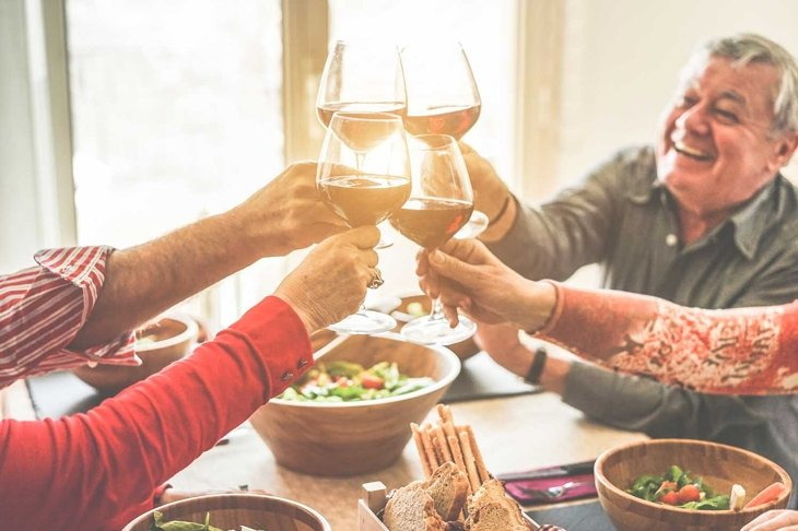 Senior friends cheering with wine glasses at home lunch - Happy mature people having fun together - Focus on left bottom glass - Joyful elderly lifestyle concept