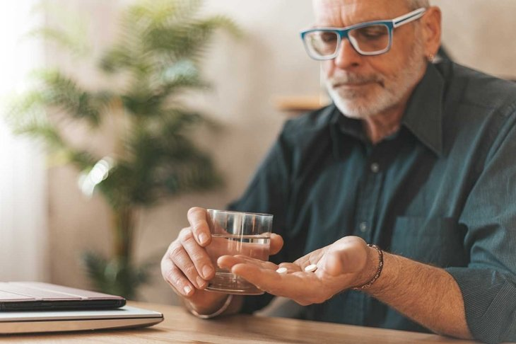 Pain medications. Senior man holding pills and a glass of water in his hands. Headache in the elderly.