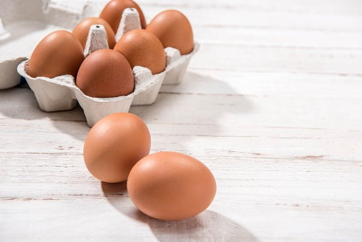 Close-up view of raw chicken eggs in egg box on white wooden background