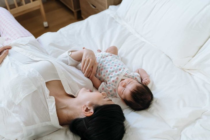 high angle view korean mother lying on bed with her young child. asian woman face to her baby daughter just put her kid to bed by singing gently to her.