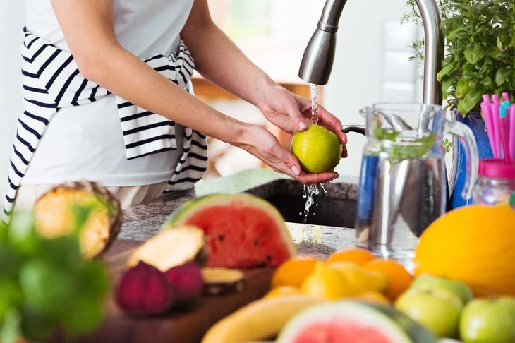 Healthy woman washing an apple above kitchen sink while preparing fresh breakfast with fruit