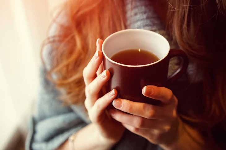 Drink Tea relax cosy photo with blurred background. Female hands holding mug of hot Tea in morning. Young woman relaxing tea cup on hand. Good morning Tea or Have a happy day message concept.
